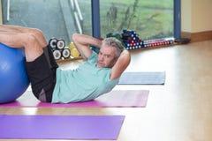 做仰卧起坐的老人在健身房 免版税库存照片