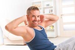 做仰卧起坐的英俊的人 免版税库存照片