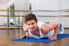 做仰卧起坐的年轻人在健身演播室 免版税库存照片
