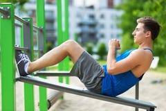 做仰卧起坐的年轻人在室外健身房 免版税库存照片