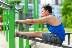 做仰卧起坐的年轻人在室外健身房 库存图片