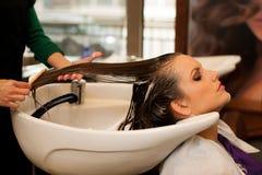 做头发治疗的美发师对沙龙的一名顾客 免版税库存图片
