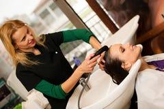 做头发治疗的美发师对沙龙的一名顾客 免版税图库摄影