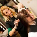 做头发治疗的美发师对沙龙的一名顾客 库存图片