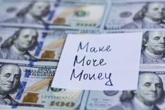 做更多金钱笔记在美金背景 免版税图库摄影