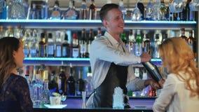 做年轻女性朋友的男服务员鸡尾酒在酒吧 免版税库存照片