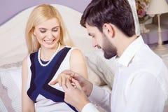 做结婚提议的英俊的人,当提供他的妻子定婚戒指时 免版税库存图片
