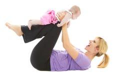 做婴孩瑜伽的年轻美丽的caucasion妈妈 免版税库存图片