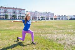 做年轻愉快的妇女舒展锻炼户外,瑜伽姿势 免版税图库摄影