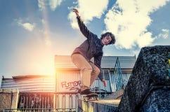 做滑板跳跃的把戏的溜冰板者在日出城市 免版税图库摄影