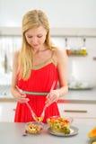 做水果沙拉的少妇在厨房里 免版税库存照片