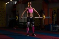 做锻炼前面蹲坐的健身妇女 免版税图库摄影