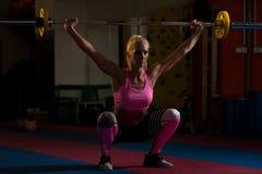 做锻炼前面蹲坐的健身妇女 库存图片
