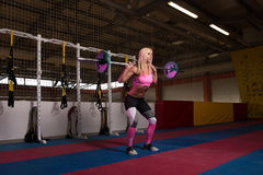做锻炼前面蹲坐的健身妇女 免版税库存照片