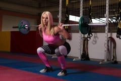 做锻炼前面蹲坐的健身妇女 免版税库存图片