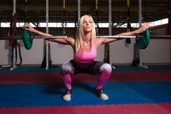 做锻炼前面蹲坐的健身妇女 库存照片