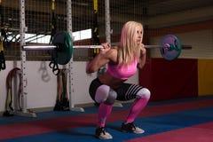 做锻炼前面蹲坐的少妇 免版税库存照片