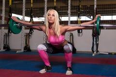 做锻炼前面蹲坐的少妇 图库摄影