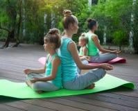 做锻炼实践的瑜伽的母亲和女儿户外 免版税库存照片