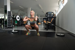做锻炼杠铃前面蹲坐的少妇 免版税库存图片