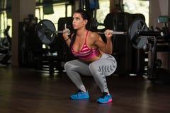 做锻炼杠铃蹲坐的拉丁妇女 库存图片