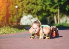 做锻炼的健身妇女在室外交叉训练锻炼期间在晴朗的早晨 库存照片