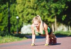做锻炼的健身妇女在室外交叉训练锻炼期间在晴朗的早晨 库存图片