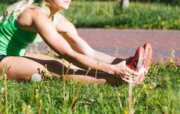 做锻炼的健身妇女在室外交叉训练锻炼期间在晴朗的早晨 免版税库存照片