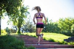 做锻炼的健身妇女在室外交叉训练锻炼期间在晴朗的早晨 免版税库存图片