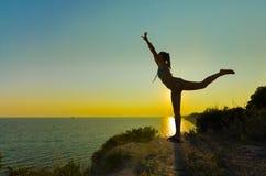 做锻炼的女孩的剪影在日落 免版税库存图片