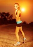做锻炼的妇女在日落 免版税库存照片