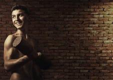 做锻炼的微笑的运动年轻爱好健美者 免版税库存照片