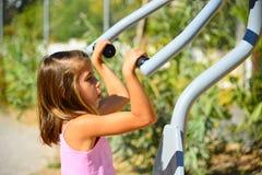 做锻炼的愉快的白肤金发的女孩在健身房公园 库存照片