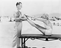做锻炼的教练员和少妇在海滩(所有人被描述不更长生存,并且庄园不存在 供应商 免版税库存图片