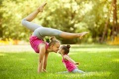 做锻炼的母亲和女儿户外 免版税库存照片