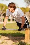 做锻炼的年轻健康人在一个公园 免版税库存图片