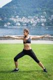 做锻炼的年轻可爱的妇女户外 免版税库存图片