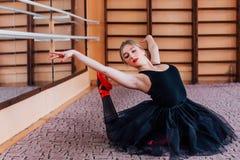 做锻炼的年轻微笑的芭蕾舞女演员在训练大厅里 图库摄影