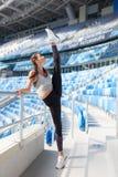做锻炼的年轻运动的女孩在体育场 她举她的腿在我的头 运动服的妇女了不起的舒展 库存图片