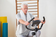 做锻炼脚踏车的老人 库存照片