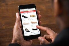 做购物在网上在移动电话的人 库存图片