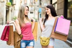 做购物的两个微笑的少妇 免版税库存照片