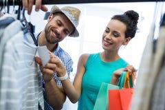 做购物的夫妇在衣裳商店 库存照片