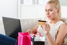 做购物的美丽的白肤金发的妇女 免版税库存图片