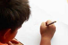 做他的图画的逗人喜爱的小男孩 库存图片
