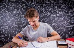 做他的家庭作业的行家学生反对一个大黑板 库存图片