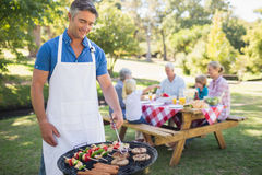 做他的家庭的愉快的人烤肉 免版税图库摄影