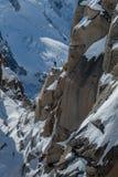 做他们的峭壁面孔的两个攀岩运动员方式在冬天 库存照片
