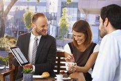做介绍的愉快的商人在早餐 免版税图库摄影