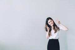 做滑稽的兔子姿势,在灰色墙壁背景的拷贝空间的逗人喜爱的亚裔大学女孩 免版税库存图片